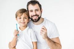 Fader och son med tandborstar Royaltyfria Bilder