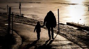 Fader och son nära en djupfryst sjö Royaltyfri Fotografi
