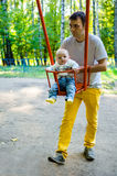 Fader och son på en gunga i en parkera Royaltyfria Bilder