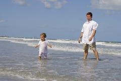 Fader och son på en strand fotografering för bildbyråer
