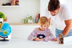 Fader och son på skrivbordet som hemma utbildar Royaltyfri Fotografi