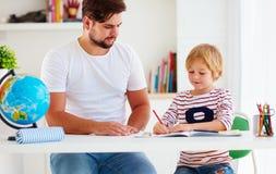 Fader och son på skrivbordet som hemma utbildar Royaltyfria Bilder