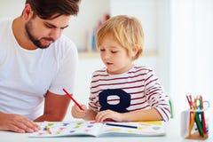 Fader och son på skrivbordet som hemma utbildar Arkivfoto