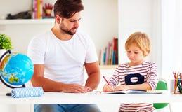 Fader och son på skrivbordet som tillsammans gör läxa Arkivfoton