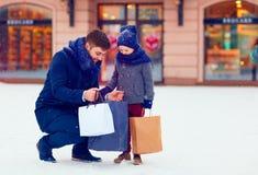 Fader och son på vintershopping i stad, semesterperiod Arkivfoto