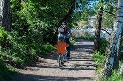 Fader och son rida cyklar arkivbild