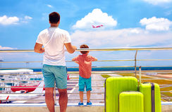 Fader och son som är klara för sommarsemester, medan vänta på att stiga ombord i internationell flygplats Arkivbild