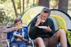 Fader och son som äter smörgåsen i skog Fotografering för Bildbyråer