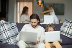 Fader och son som använder bärbara datorer som hemma sitter på soffan Arkivfoto
