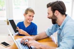 Fader och son som använder bärbara datorn och den digitala minnestavlan Royaltyfria Foton