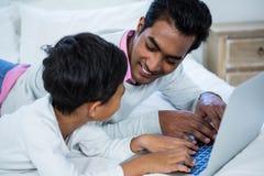 Fader och son som använder bärbara datorn på säng Royaltyfria Bilder