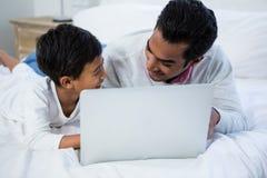 Fader och son som använder bärbara datorn på säng Arkivbild