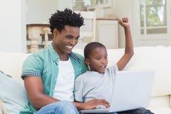 Fader och son som använder bärbara datorn på soffan Arkivfoto