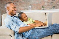 Fader och son som använder bärbara datorn på soffan Arkivbilder