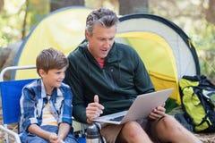 Fader och son som använder bärbara datorn vid tältet i skog Royaltyfri Foto