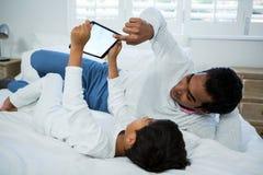 Fader och son som använder den digitala minnestavlan på säng Royaltyfria Foton