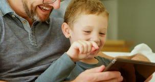 Fader och son som använder den digitala minnestavlan på soffan hemmastadd 4k