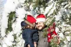 Fader och son som bär den Santa Claus hatten Royaltyfria Foton
