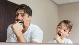 Fader och son som borstar tänder i badrum Arkivfoto