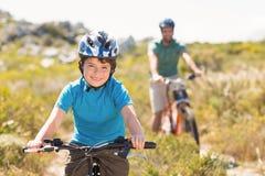 Fader och son som cyklar till och med berg arkivbild