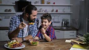 Fader och son som förbereder fruktsteknålar i kök arkivfilmer
