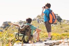 Fader och son som fotvandrar till och med berg royaltyfri foto