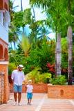 Fader och son som går på den gulliga tropiska gatan Arkivfoto
