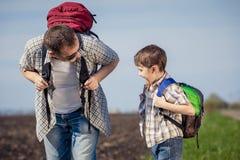 Fader och son som går på vägen på dagtiden Arkivfoton