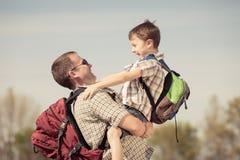 Fader och son som går på vägen på dagtiden Royaltyfri Bild