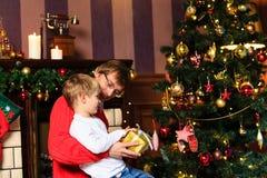 Fader och son som ger gåvor i jul Arkivfoton