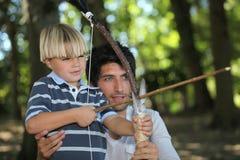 Fader och son som gör bågskytte Arkivbilder