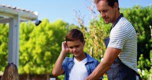Fader och son som grillar korvar och havre på grillfest arkivfilmer