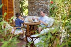Fader och son som har frukosten tillsammans Arkivbilder