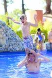Fader och son som har gyckel i simbassäng Arkivfoton