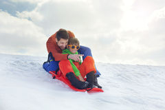 Fader och son som har gyckel i snön som glider Royaltyfri Bild