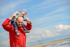 Fader och son som har gyckel på den tropiska stranden Fotografering för Bildbyråer