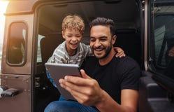 Fader och son som har gyckel på vägtur med den digitala minnestavlan royaltyfri foto
