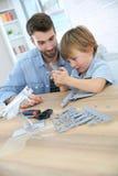 Fader och son som har gyckel som monterar ett flygplan Arkivfoton