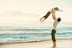 Fader och son som har gyckel tillsammans i solnedgånghavet Royaltyfria Bilder