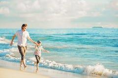 Fader och son som har stor familjtid på havet Arkivbilder