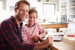 Fader och son som hemma använder bärbar datordatoren Arkivbilder