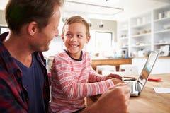 Fader och son som hemma använder bärbar datordatoren Arkivfoto
