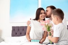 Fader och son som hemma gratulerar mamman lycklig moder s f?r dag royaltyfri fotografi