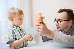 Fader och son som hemma spelar med bolllera Royaltyfri Fotografi