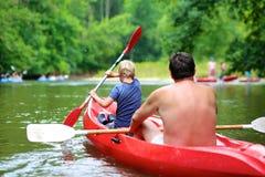 Fader och son som kayaking på floden Royaltyfria Bilder