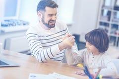 Fader och son som konkurrerar i armbrottning arkivbild