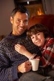 Fader och Son som kopplar av med den hållande ögonen på TV:N för varm drink Royaltyfri Bild