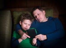 Fader och son som ligger på soffan med enavläsare. Fotografering för Bildbyråer