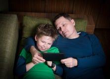 Fader och son som ligger på soffan med enavläsare. Arkivfoto