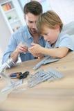 Fader och son som monterar ett flygplan Arkivfoto